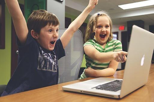 Kids working at computers at school with boy raising his arms in excitement